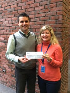 Eric Proulx of Tanger Outlets, Tilton, NH, presents a donation to NHBCC Board member Tiffany Fuller.